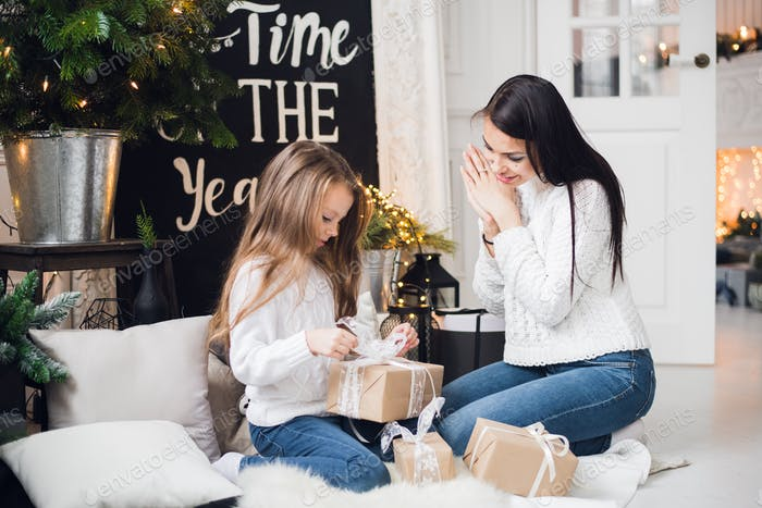 Merry Christmas and Happy Holidays. Cheerful mom and her cute daughter girl opening a Christmas