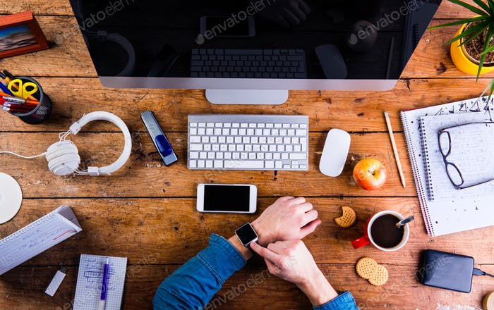Business person working at office desk wearing smart watch