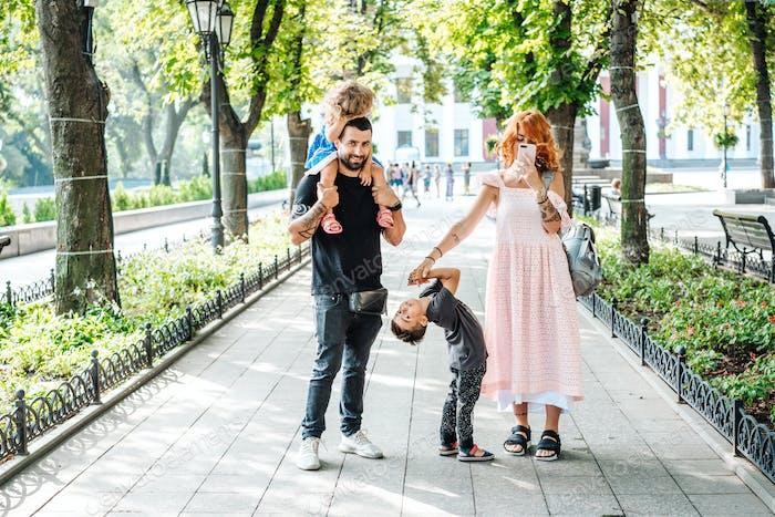 Glückliche schöne Familie zu Fuß im Park