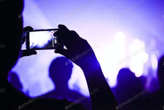 Someone talking a picture during a concert