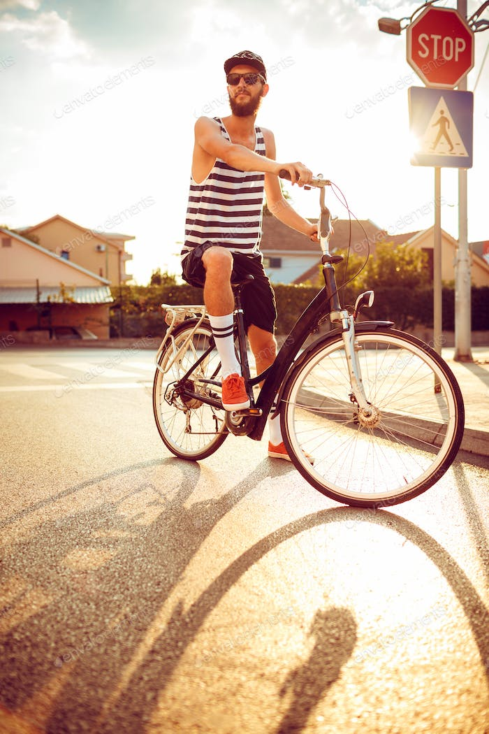Young man in sunglasses riding a bicycle on a city street at sun