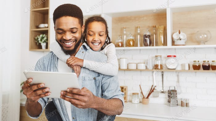 Daddy and daughter having video call on tablet in kitchen
