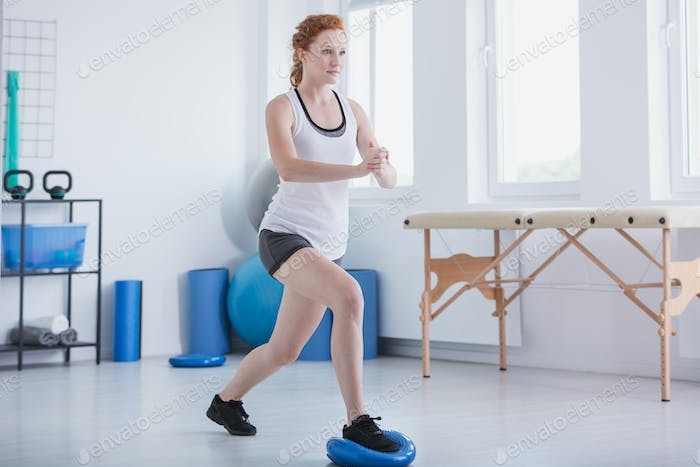 Sportswoman exercising in gymnastic room with equipment during p