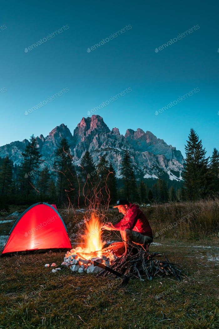 Man Warming Hands vom Lagerfeuer in den Bergen. Rot beleuchtetes Zelt