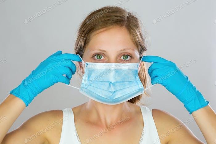 Blonde Frau trägt blaue Gesichtsmaske mit weißem Hintergrund
