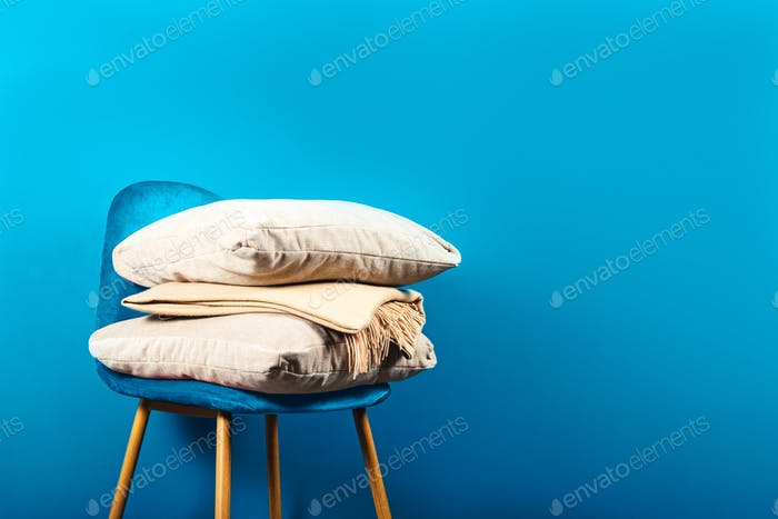 Modern Blue Velour Chair with Beige Cushions and Throw