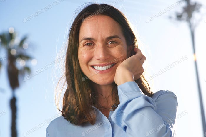 Close up happy older woman laughing Wirth hand in hair outside