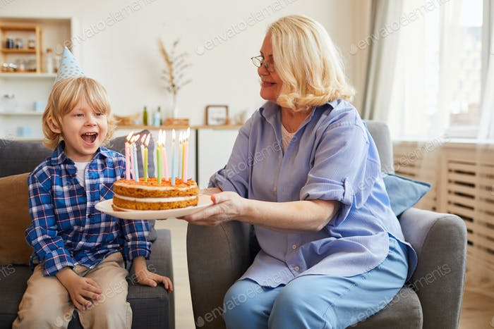 Grandmother cooking cake for grandson