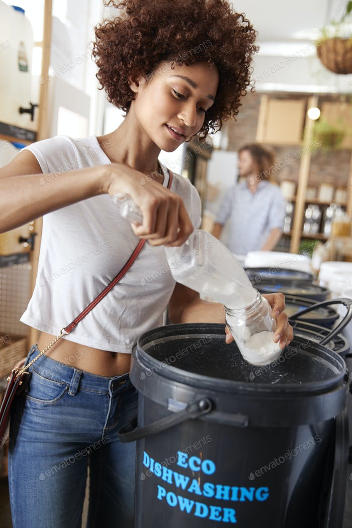 Woman Filling Container With Dishwasher Powder In Plastic Free Grocery Store