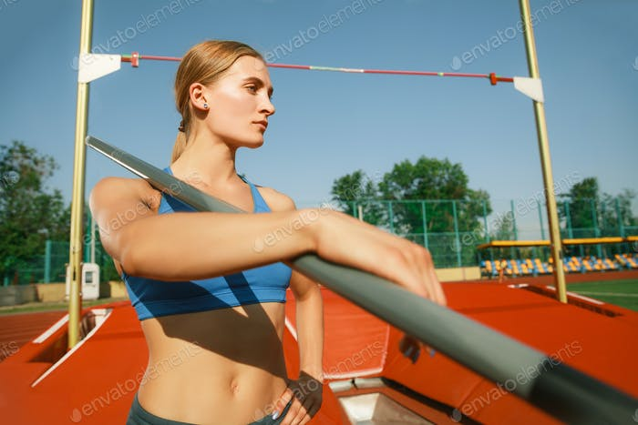 Female high jumper training at the stadium in sunny day