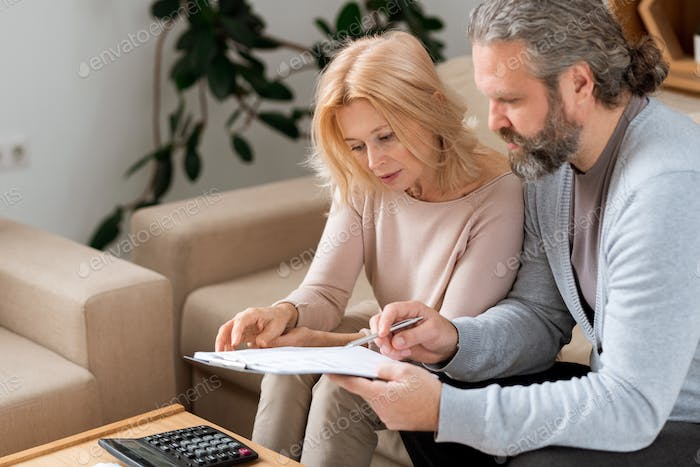Bearded mature man pointing at contract while reading it with his wife