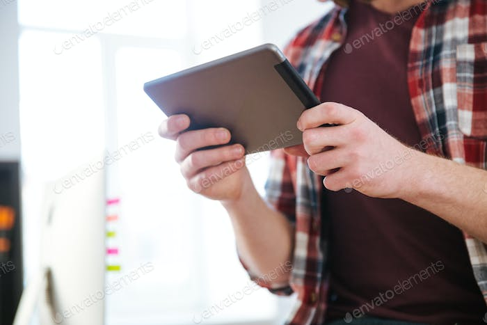 Closeup of tablet used by man in checkered shirt