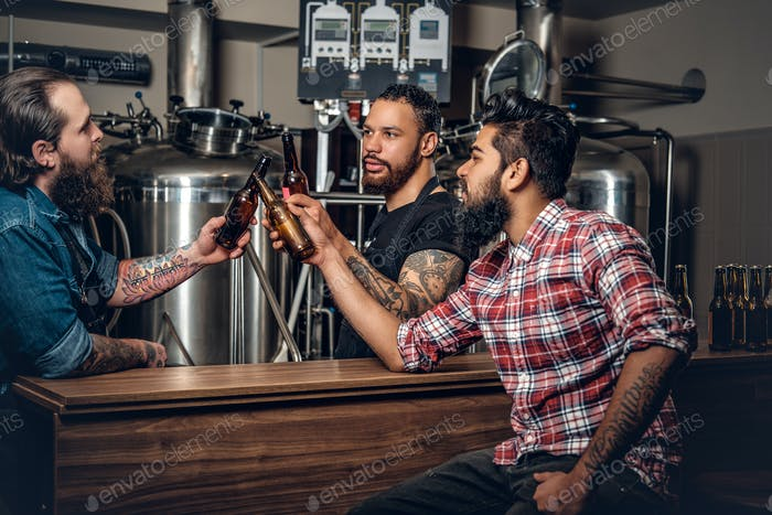 Stylishthree men men drinking craft beer in the microbrewery.