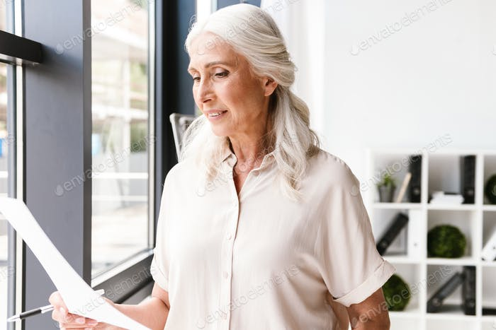 Attractive mature business woman analyzing documents