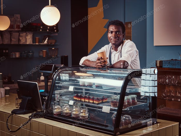 African barista relaxing after workday with coffee while leaning on the counter at coffee shop.