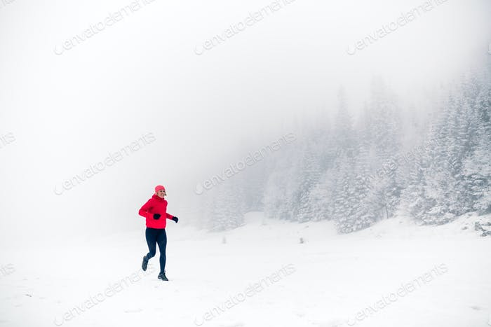 Trail running on snow in winter mountains
