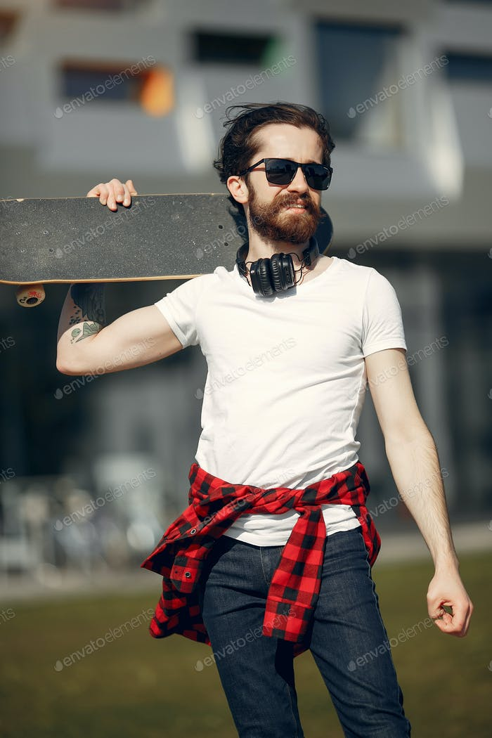 Stylish guy with skate in a summer city