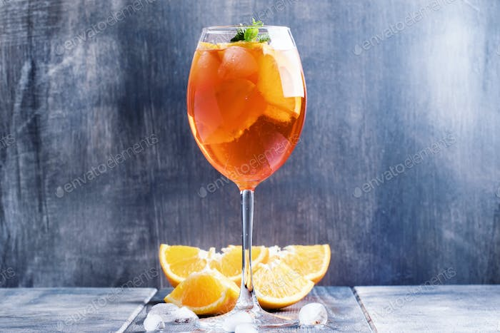 Summer cocktail aperitif with orange bitter, fruit, ice and soda in tall glass