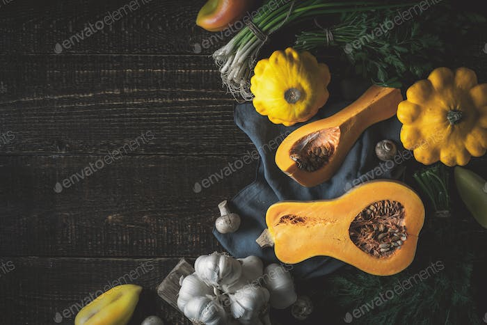 Pumpkin with different vegetables  at the right of the  wooden table