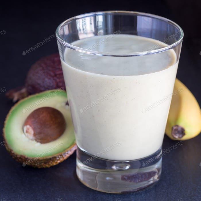 Smoothie with avocado, banana, milk and honey on dark slate back