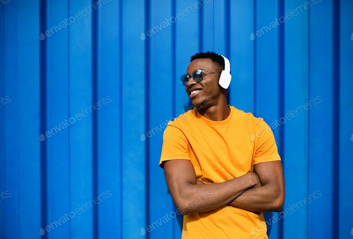 Young black man with headphones standing against blue background, black lives matter concept