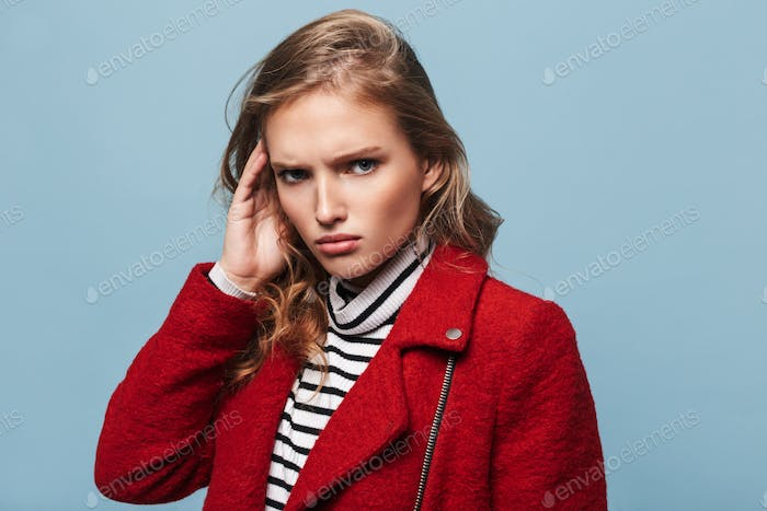 Stylish angry woman with wavy hair in red jacket sadly looking in camera over blue background