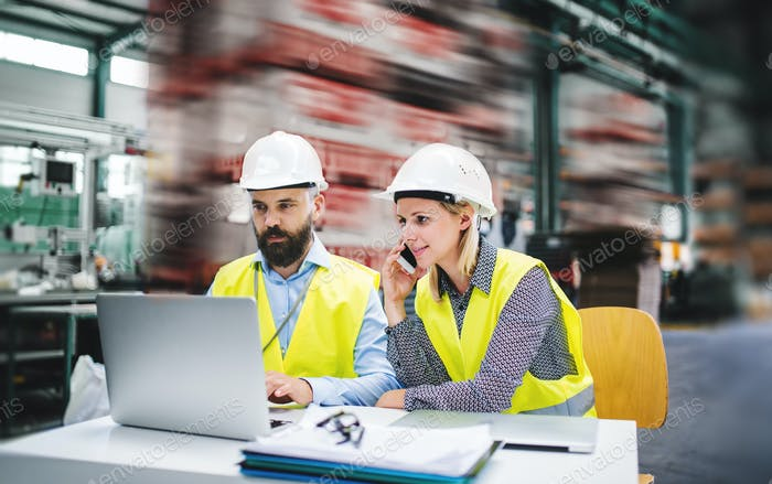 A portrait of an industrial man and woman engineer with laptop in a factory, working.