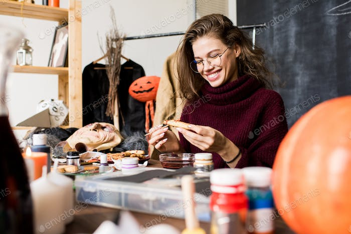 Excited lady making Halloween cookie more realistic