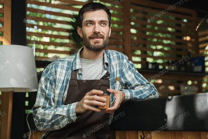Image of excited waiter boy sitting at the bar while working in