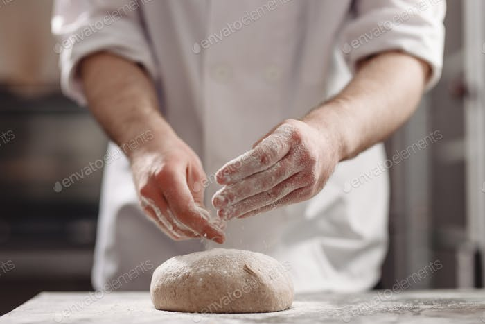 Baker kneads dough on the table in the bakery