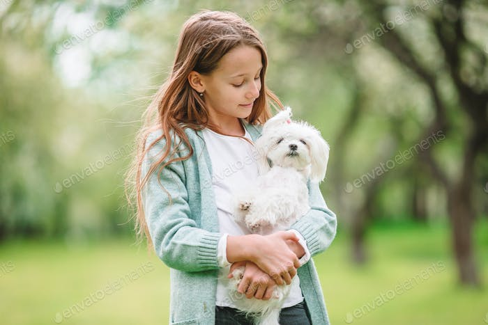 Little smiling girl playing and hugging puppy in the park
