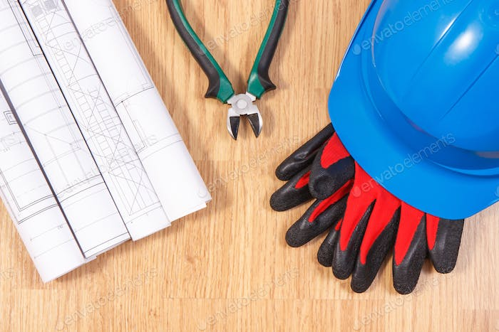 Electrical drawings, protective helmet with gloves and work tools, accessories for engineer jobs