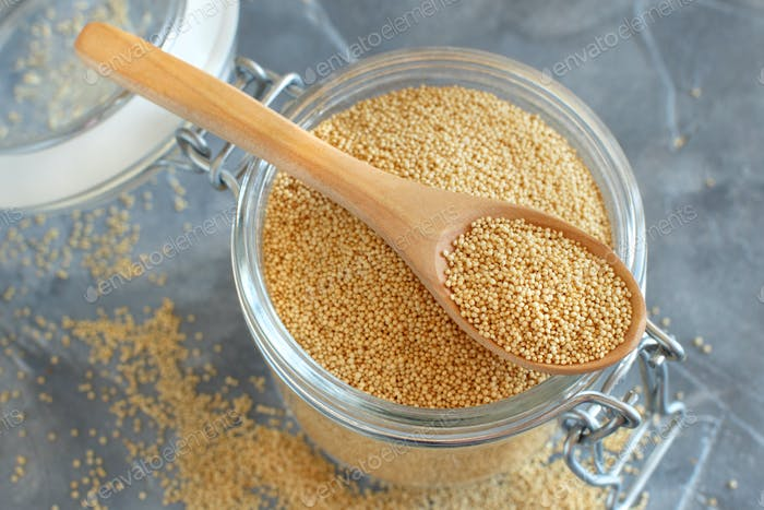 Glass jar of raw Amaranth Grain with a spoon