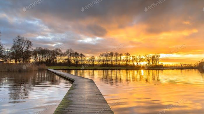 Holzsteg im See unter orangefarbenem Sonnenuntergang