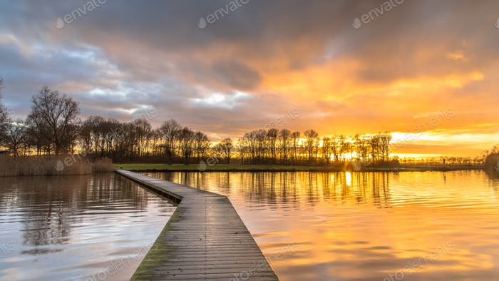 Wooden walkway in lake under orange sunset