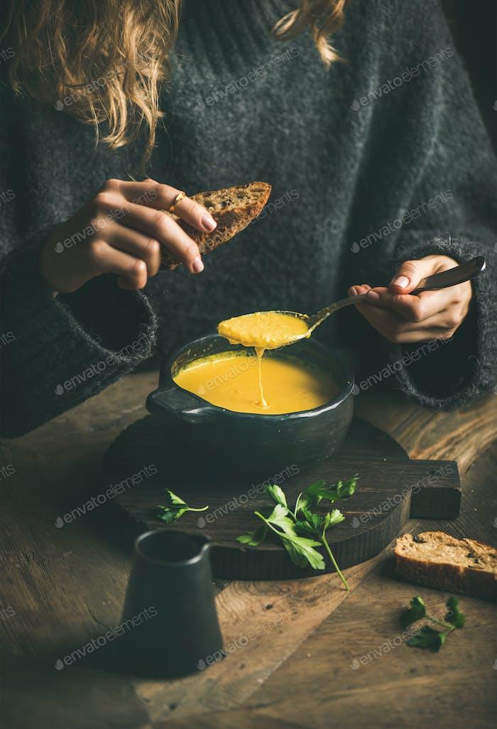 Frau im Winter Pullover essen süße Maissuppe aus Schüssel