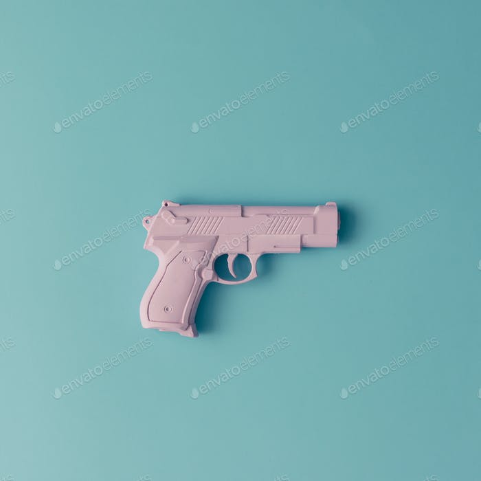 Pink hipster handgun on blue pastel background. Minimal flat lay concept.