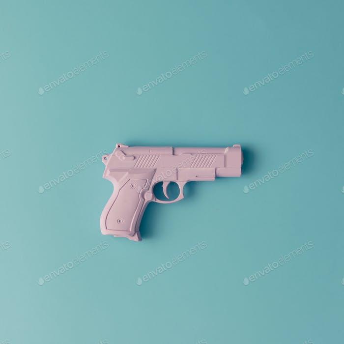 Rosa Hipster Handfeuerwaffe auf blauem Pastellgrund. Minimales flaches Laienkonzept.