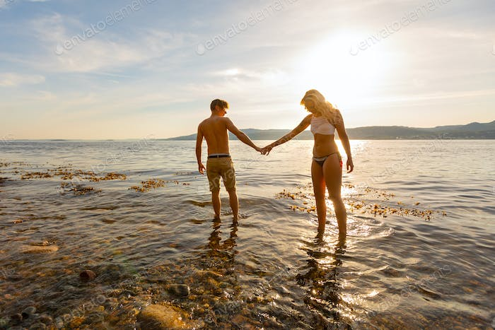 Beautiful couple holding hands and walks at the sea shore in the evening