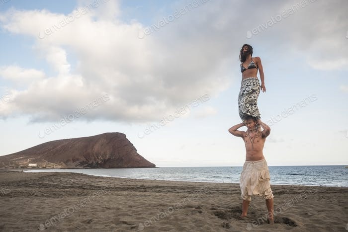 acrobatic balnced position for beautiful brave couple man and woman at the beach