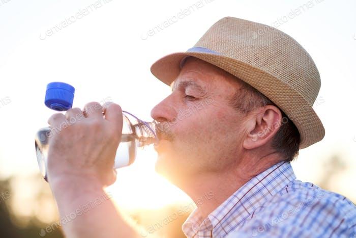 Senior hispanic Mann im Sommer Hut trinken Süßwasser