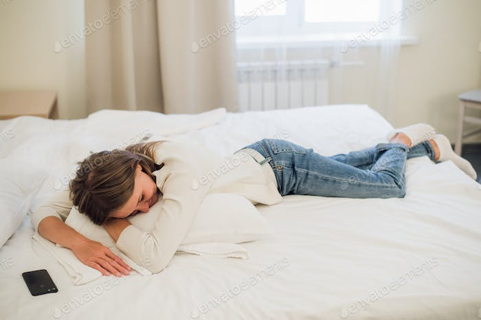 Relaxed young pretty woman sleeping in bed with blank screen mobile phone