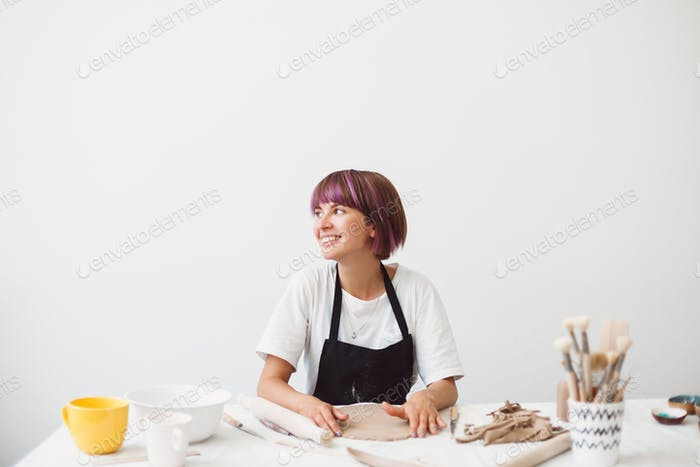 Girl with colorful hair in black apron and white T-shirt working with clay happily looking aside