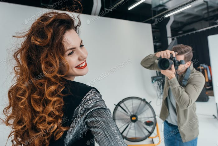 professional photographer and beautiful model on fashion shoot in photo studio with fan