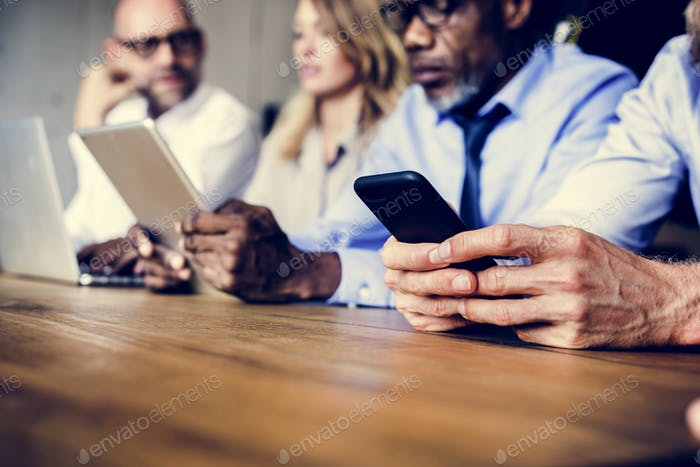 Business people in a meeting using devices