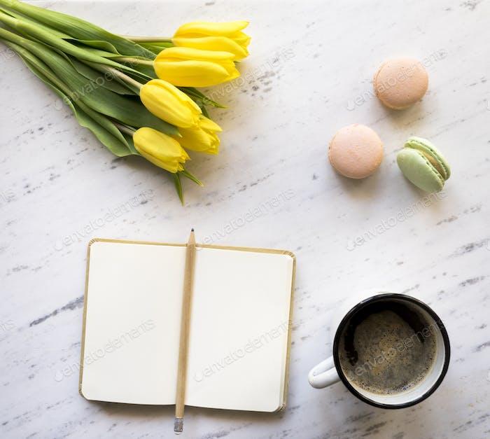 Vista superior del cuaderno, café, macarons y tulipanes en el fondo de mármol