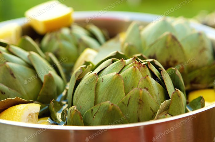 Close up of artichokes and lemon in a pot