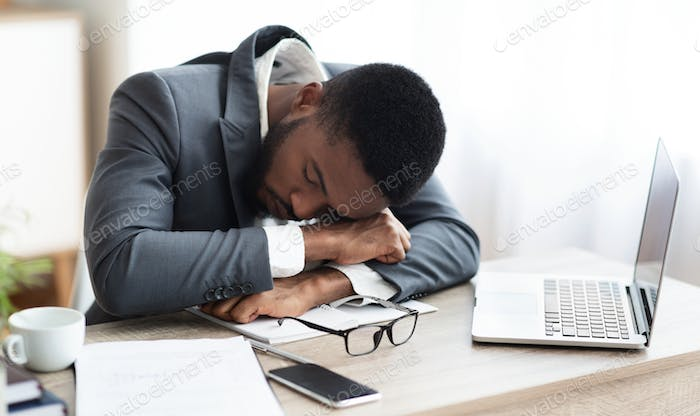 Tired african american businessman having a nap at workplace