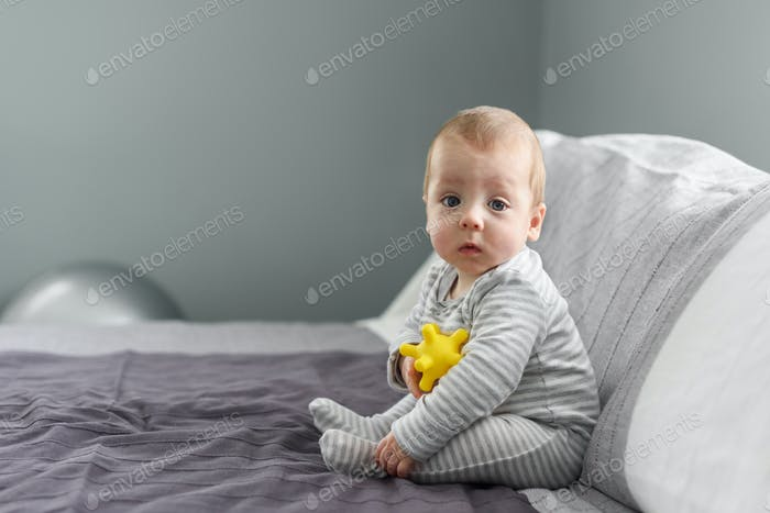 Sitting baby boy on grey carpet closeup