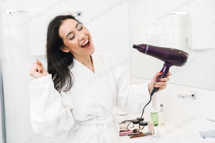 Mujer joven optimista cabello seco con secador de pelo.